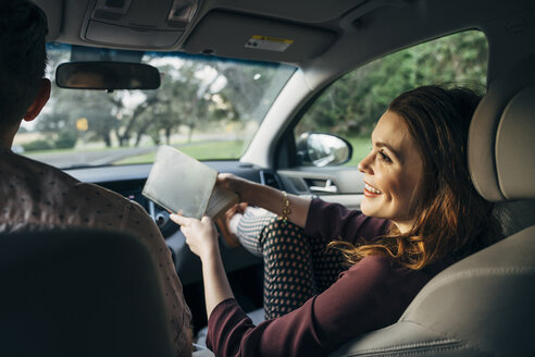 Smiling wife holding book while talking to husband in car - CAVF54122