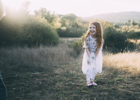 Cheerful girl looking away while standing on field at park - CAVF54158