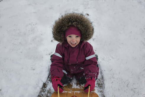 High angle portrait of girl tobogganing on snow covered field - CAVF54185