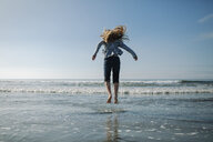 Rear view of playful girl jumping on shore at beach against sky - CAVF54206