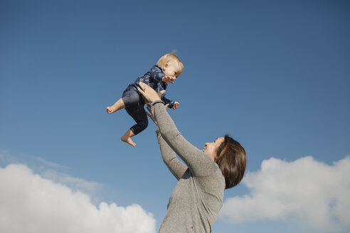Low angle view of playful mother throwing daughter in air against sky - CAVF54209