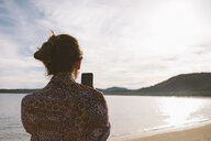 Rear view of woman photographing with mobile phone at beach against cloudy sky - CAVF54236