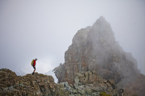 Side view of hiker with backpack standing on mountain amidst clouds - CAVF54260