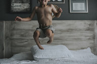 Playful shirtless boy jumping on bed at home - CAVF54314