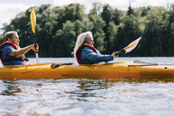 Side view of senior couple kayaking on lake against sky - CAVF54356