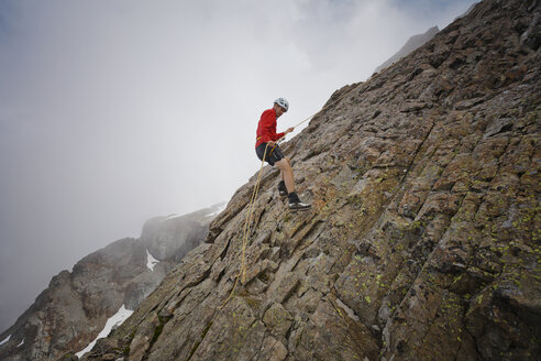 Side view of hiker using rope while climbing rock formations against clouds - CAVF54365
