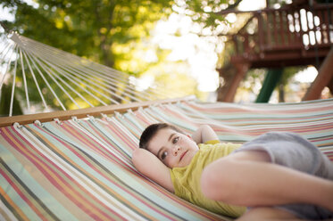 Thoughtful boy with hands behind head lying in hammock at park - CAVF54380