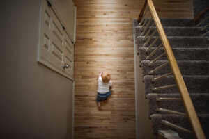 Overhead view of baby boy crawling on hardwood floor at home - CAVF54383