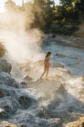 High angle view of woman walking on rock in steam emitting thermal pool - CAVF54386