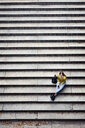 High angle view of woman with phone sitting on steps at park - CAVF54470