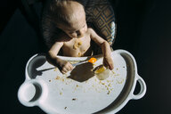 High angle view of shirtless baby boy eating food while sitting on high chair at home - CAVF54515