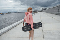 Young woman holding skateboard walking at the riverside - VPIF00984