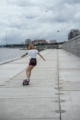 Rear view of young woman riding carver skateboard at the riverside - VPIF00987
