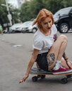 Young woman riding on carver skateboard on a street - VPIF01002