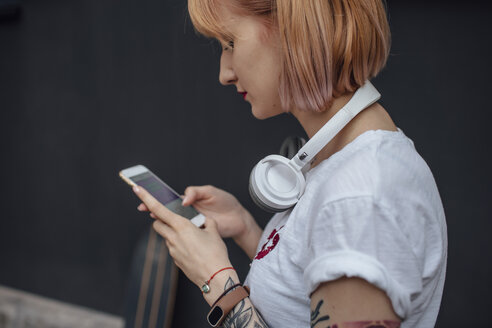 Young woman with headphones using cell phone - VPIF01020