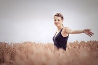 A beautiful happy free young woman embracing nature in a field - INGF07202