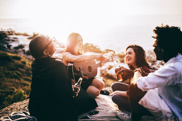 Friends sitting down playing the guitar during sunset - INGF07436