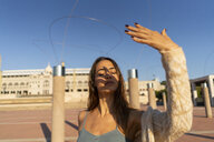Spain, Barcelona, Montjuic, young woman raising her hand in sunlight - AFV01950