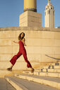 Spain, Barcelona, Montjuic, young woman wearing red jumpsuit jumping on stairs - AFVF01956