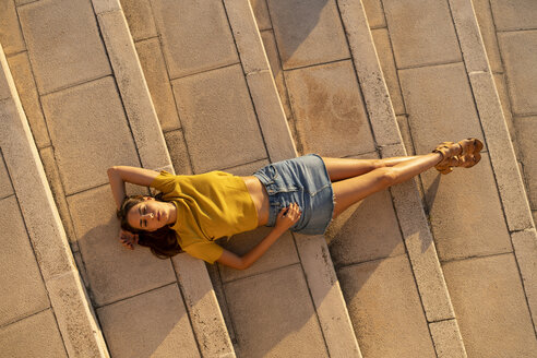 Young woman lying on steps outdoors - AFVF01959
