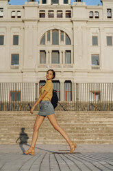 Spain, Barcelona, Montjuic, portrait of young woman passing a building - AFVF01962