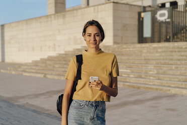 Portrait of smiling young woman holding cell phone outdoors - AFVF01965