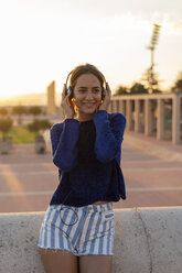 Spain, Barcelona, Montjuic, smiling young woman listening to music with headphones at sunset - AFVF01968