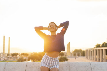 Spain, Barcelona, Montjuic, happy young woman listening to music with headphones at sunset - AFVF01971