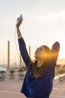 Spain, Barcelona, Montjuic, happy young woman listening to music with headphones at sunset - AFVF01974