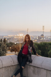 Spain, Barcelona, Montjuic, young woman leaning against a wall at dusk with city lights in background - AFVF01980