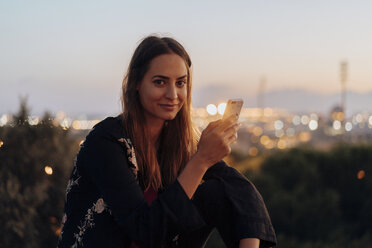 Spain, Barcelona, Montjuic, portrait of smiling young woman at dusk with cell phone - AFVF01986