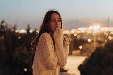Spain, Barcelona, Montjuic, portrait of young woman at dusk with city lights in background - AFVF01989