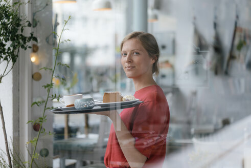 Portrait of smiling young woman serving coffee and cake in a cafe - KNSF05290