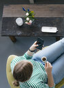 Overhead view of young woman with cell phone and espresso in a cafe - KNSF05299