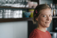 Portrait of smiling young woman in a cafe - KNSF05302