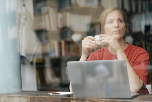 Young woman with cup of coffee and laptop in a cafe - KNSF05308