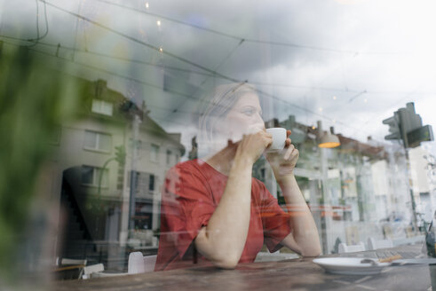 Young woman with cup of coffee behind windowpane in a cafe - KNSF05311