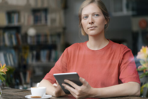 Young woman using tablet at the window in a cafe - KNSF05314