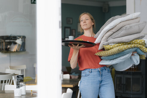 Young woman holding tray and cushions in a cafe - KNSF05335