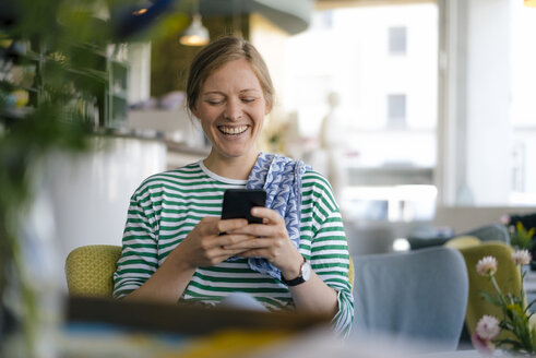 Laughing young woman looking on cell phone in a cafe - KNSF05353
