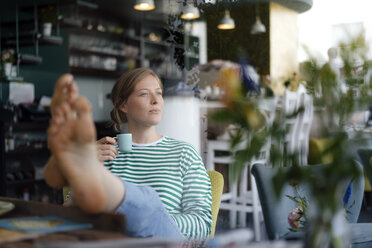 Young woman with feet up holding espresso cup in a cafe - KNSF05356