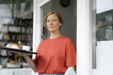 Portrait of young woman serving coffee and cake in a cafe - KNSF05368