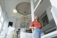 Low angle view of young woman standing in a cafe - KNSF05374