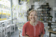Portrait of happy young woman posing behind windowpane in a cafe - KNSF05377