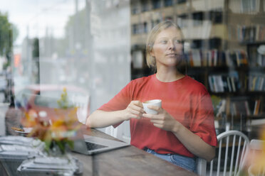 Young woman with laptop and coffee cup in a cafe - KNSF05380