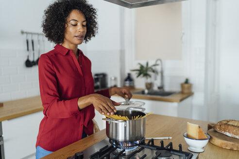 Woman standing in kitchen, preparing spaghetti - BOYF00959