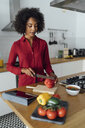 Woman standing in kitchen, chopping vegetables - BOYF00962