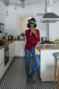 Woman standing in her kitchen, wearing VR goggles, drinking orange juice - BOYF00998