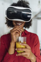 Woman standing in her kitchen, wearing VR goggles, drinking orange juice - BOYF01001