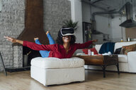 Woman lying on seating furniture, wearing VR goggles, pretending to fly - BOYF01004
